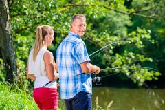 Young couple fishing or angling standing on river shore. In grass Royalty Free Stock Photos