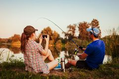 Young couple fishing and drinking tea on river at sunset. Woman filming her boyfriend catching fish. People having fun. Outdoors stock photos