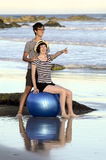 Young couple with fitness ball on beach Royalty Free Stock Photo