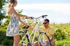 Young couple fixing bicycle on country road Royalty Free Stock Image