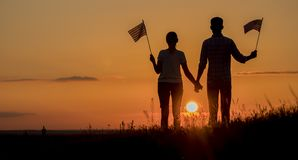 A young couple with flags of America stands in a beautiful place at sunset stock photography