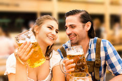 Young couple flirting in Oktoberfest beer tent while drinking beer Royalty Free Stock Photos