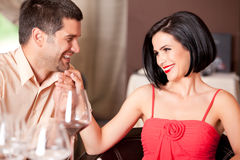 Young couple flirting at restaurant table. Happy couple flirting at restaurant table Stock Photo