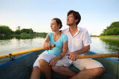 Young couple floating down the river on a boat. With oars stock image