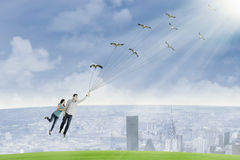 Young couple is flying by holding birds Royalty Free Stock Photo