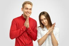 Young couple folded their hands in front of them signs of prayer and looks at the camera with a pleading expression. royalty free stock photo