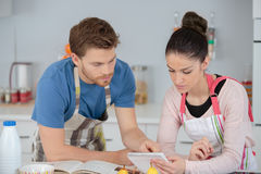 Young couple following recipe in kitchen. Young couple following a recipe in a kitchen Royalty Free Stock Images