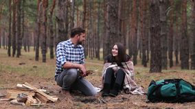 Young couple in the forest. A man is building a fire. Young couple in the forest. A man lights a fire, stealing dry firewood, the girl is sitting wrapped in a stock footage