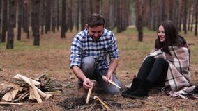 Young couple in the forest. A man is building a fire. Young couple in the forest. A man lights a fire, stealing dry firewood, the girl is sitting wrapped in a stock video