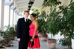 Young Couple  in formal attire peeking out. Young Couple  in formal attire ready for the prom or a wedding.  They are peeking out from behind a column Stock Photography