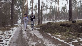 Young couple of friends runs in the morning in the forest. Young sport people makes morning exercises outdoors. Pretty woman and handsome man wearing sport stock video
