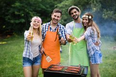 Young couple with friends smiles and making roasted barbecue in campground. Young women and men smiles and making roasted barbecue in campground royalty free stock images