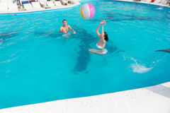 Young couple frolicking in a pool. Young couple frolicking in a turquoise blue swimming pool throwing a colorful beach ball to each other Royalty Free Stock Image