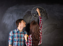 Young Couple in Front Black Chalkboard stock photography