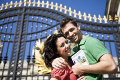 A young couple in front of Buckingham Palace, holding a guidebook royalty free stock image