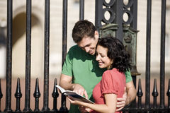 A young couple in front of Buckingham Palace, reading a guidebook Royalty Free Stock Image