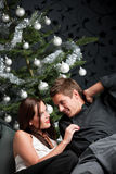 Young couple in front of Christmas tree Stock Photos