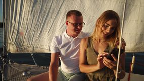 Young couple traveling by yacht and using cellphone. Young couple on the front deck of sailing yacht. Woman using mobile to look at photos they made during the stock video