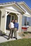Young couple in front of new house Royalty Free Stock Photo