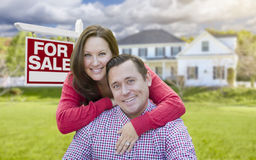 Young Couple In Front of For Sale Sign and House Royalty Free Stock Image