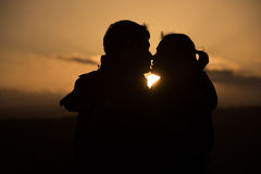 Young couple in front of sunset Royalty Free Stock Photos
