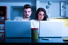 Young couple in front of their Laptop Computers at home Royalty Free Stock Images