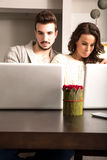 Young couple in front of their Laptop Computers at home Stock Images