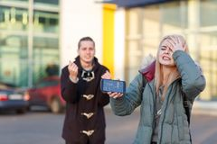 A young couple with frustrated emotions because of a broken smartphone stand on the street. A young European couple with frustrated emotions because of a modern Royalty Free Stock Photos