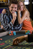 Young couple gambling, man with gambling chip, smiling, portrait Stock Photo