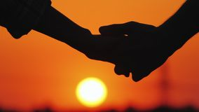 A young couple gently holding hands on the background of a large orange sun disc royalty free stock image