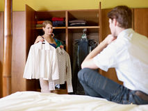 Young couple getting dressed. Caucasian couple getting dressed in the morning, with woman choosing shirt. Horizontal shape, front view, three quarter length Royalty Free Stock Photography
