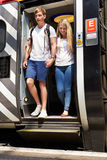 Young Couple Getting Off Train At Platform. Edge Stock Photography
