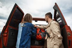 Young couple getting their backpacks from the trunk royalty free stock photos