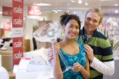 Young couple with giant cocktail glass in shop, smiling, portrait royalty free stock photo