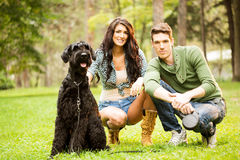 Young Couple With Giant Schnauzer Stock Photography