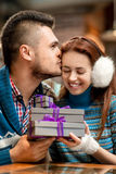 Young couple with gift boxes at the cafe in winter Royalty Free Stock Photography