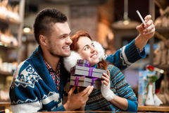 Young couple with gift boxes at the cafe in winter Stock Image