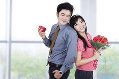 Young Couple with A Giftbox and Flowers Royalty Free Stock Photos