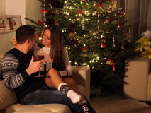 Young couple with gifts in front of Christmas tree Stock Photography