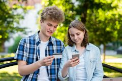 Young couple girl and boy. In summer in the park in nature. Holds a smartphone on a credit card. Do shopping on the. Young couple girl and boy. In the summer in royalty free stock photography