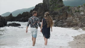 Young couple girl and man walking along the beach, rear view. Beautiful view of the ocean and large rocks stock footage
