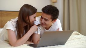Young couple of girls and guy lying on bed in front of laptop in light bedroom. Pretty young woman flirts with her boyfriend and tickles his face gently with stock footage