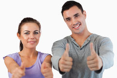 Young couple giving thumbs up. Against a white background Stock Photos