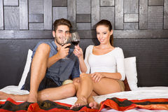A young couple with a glass of wine in an asian style hotel room Stock Photo