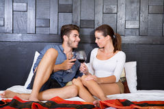 A young couple with a glass of wine in an asian style hotel room Stock Images