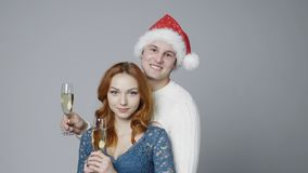 Young couple with glasses of champagne. Man wearing Santa hat, looking at camera and lifting glasses cheering stock footage