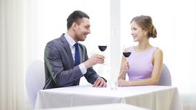 Young couple with glasses of wine at restaurant. Restaurant, couple and holiday concept - smiling young couple with glasses of red wine, talking and drinking stock video footage