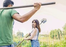 Young couple go to work in your garden. Young couple going to work in the early morning in your garden with shovel Stock Photos