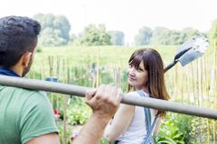 Young couple go to work in your garden. Portrait of young couple relaxing to work in the early morning in your garden with shovel Royalty Free Stock Photos