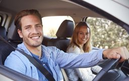 Young couple going on holiday in a car smiling to camera Stock Photos